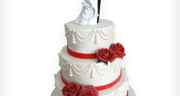 Weiße Hochzeitstorte mit roten Rosen und Perlen